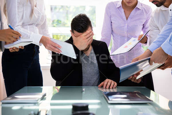 Stressed Businessman Surrounded By His Colleagues Stock photo © AndreyPopov