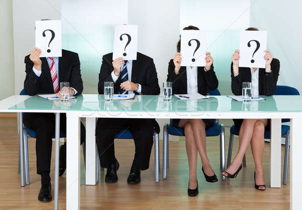 Row of businesspeople with question marks Stock photo © AndreyPopov