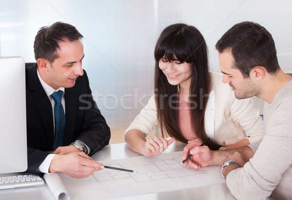 Happy Young Couple Discussing With Consultant Stock photo © AndreyPopov