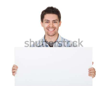 Smiling casual man with blank sign Stock photo © AndreyPopov