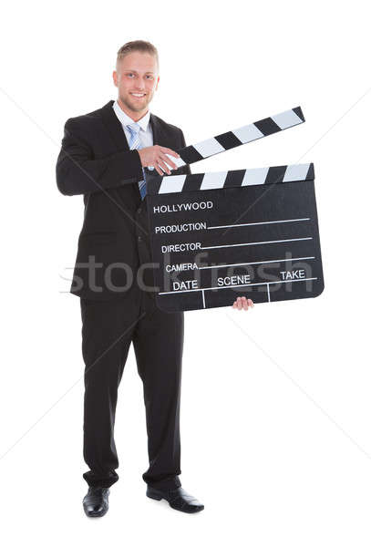 Businessman holding a blank clapper board with the arm Stock photo © AndreyPopov