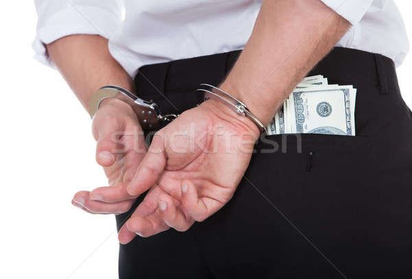 Man in handcuffs with banknotes in his pocket Stock photo © AndreyPopov