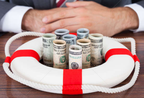 Businessman Protecting Rolled Bank Notes With Lifebuoy Stock photo © AndreyPopov