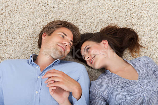 Loving Couple Looking At Each Other While Lying On Rug Stock photo © AndreyPopov