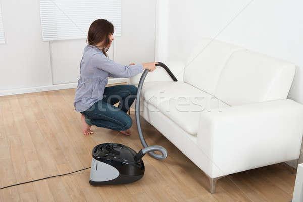 Young Woman Vacuuming Sofa At Home Stock photo © AndreyPopov