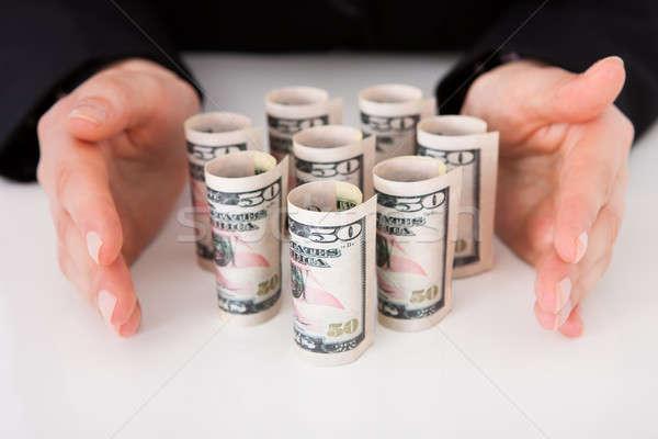 Businesswoman Shielding Rolled Dollar Bills Stock photo © AndreyPopov