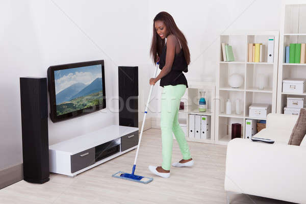 Woman Cleaning Floor In Living Room Stock photo © AndreyPopov