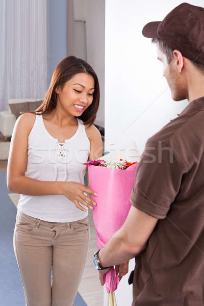 Woman Receiving Bouquet From Delivery Man Stock photo © AndreyPopov