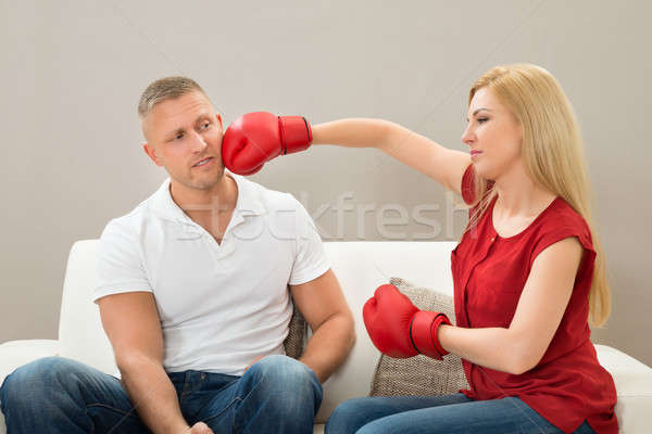 Stock photo: Couple On Sofa Fighting With Boxing Gloves