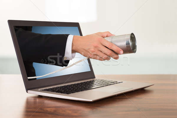 Businessperson Hand With Cans Phone From Laptop Stock photo © AndreyPopov