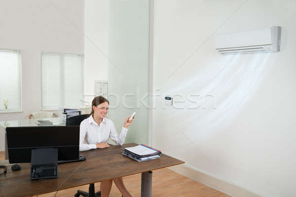 Businesswoman Operating Air Conditioner In Office Stock photo © AndreyPopov
