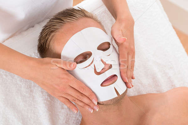 Young Man In Spa Salon With Facial Mask Stock photo © AndreyPopov