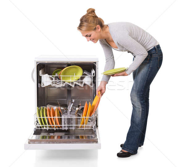 Woman Arranging Utensils In Dishwasher Over White Background Stock photo © AndreyPopov