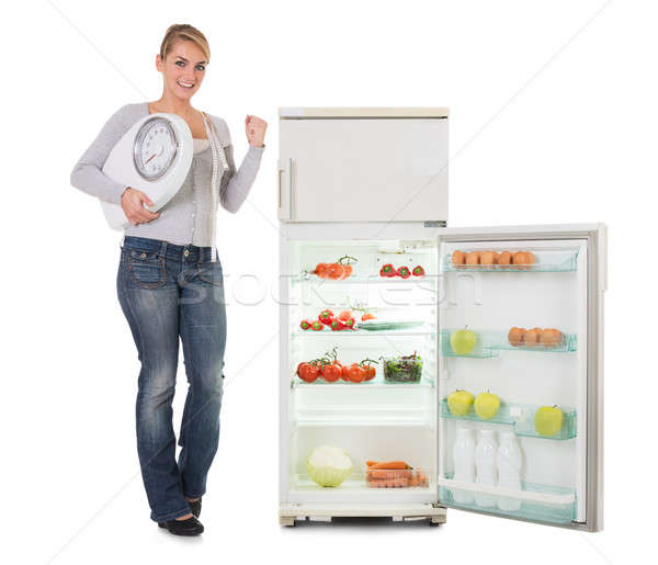 Woman Holding Weighing Scale While Standing By Refrigerator Stock photo © AndreyPopov