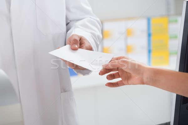 Woman Giving Prescription Paper To Pharmacist Stock photo © AndreyPopov