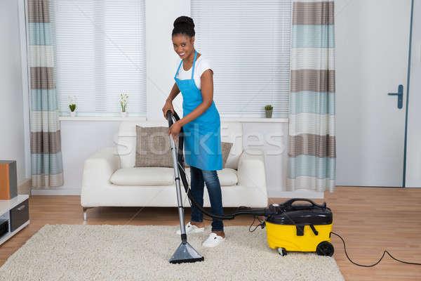 Mulher limpeza tapete aspirador de pó sorridente jovem Foto stock © AndreyPopov