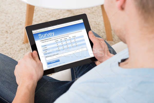 Man Filling Survey Form Online On Digital Tablet At Home Stock photo © AndreyPopov