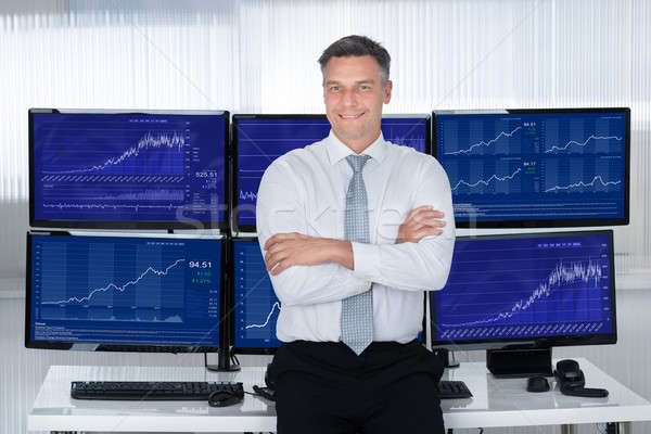 Confident Stock Market Broker Leaning On Desk Stock photo © AndreyPopov