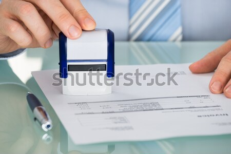 Person's Hand Pressing Stamper On Document Stock photo © AndreyPopov