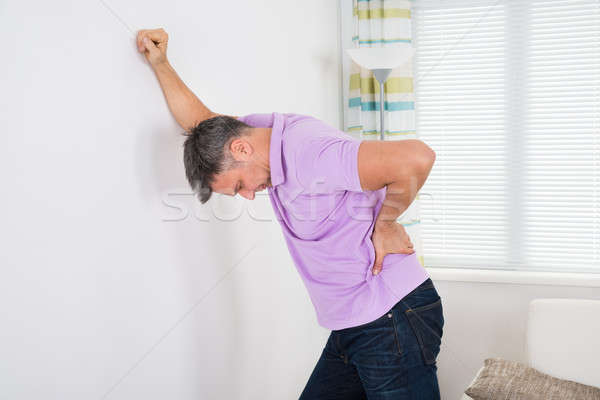 Man Having Backache While Leaning On White Wall Stock photo © AndreyPopov