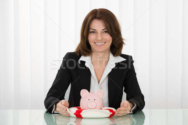 Businesswoman Sheltering Piggybank With Lifebelt Stock photo © AndreyPopov