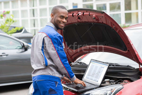 Mechanic With Laptop In Front Of Car Engine Stock photo © AndreyPopov