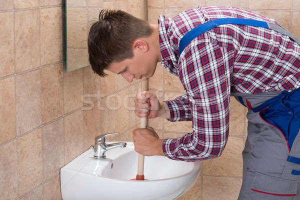 Plumber Using Plunger In Bathroom Sink Stock photo © AndreyPopov