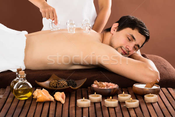 Person's Hand Giving Cupping Treatment To Man Stock photo © AndreyPopov