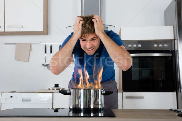 Young Male Looking At Cooking Pan On Fire Stock photo © AndreyPopov