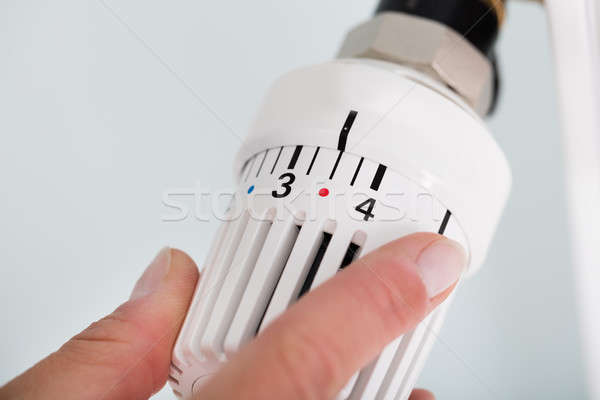 Person Adjusting Thermostat Radiator Valve Stock photo © AndreyPopov
