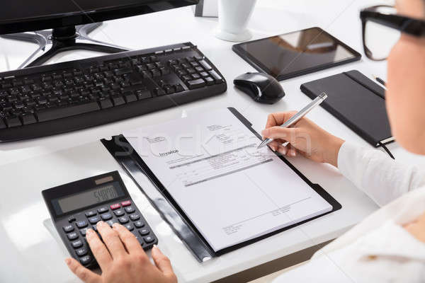 Businesswoman Using Calculator While Calculating On Invoice Stock photo © AndreyPopov