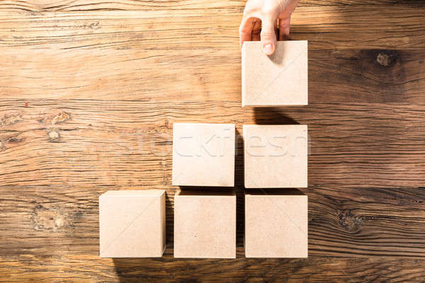 Person's Hand Arranging Wooden Block Stock photo © AndreyPopov
