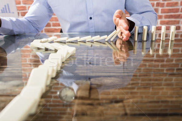Businessman Stop Dominoes On Desk Stock photo © AndreyPopov