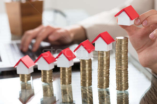 Stock photo: Miniature Houses Over The Stack Of Coins On Wooden Table