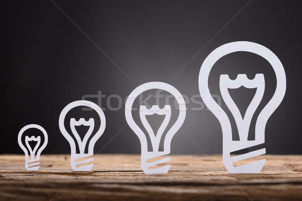 Paper Light Bulbs Arranged In Increasing Order On Table Stock photo © AndreyPopov