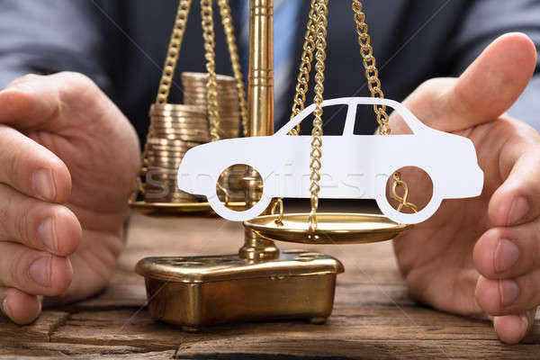 Businessman Covering Paper Car And Coins On Weighing Scale Stock photo © AndreyPopov