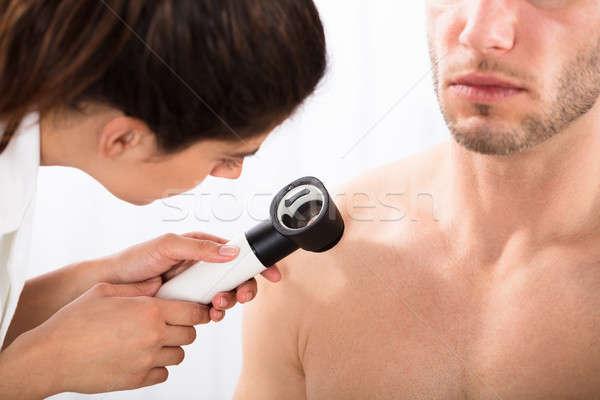 Doctor Examining Man's Shoulder With Dermatoscope Stock photo © AndreyPopov