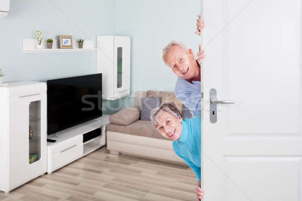 Senior Couple Peeking From Door Stock photo © AndreyPopov