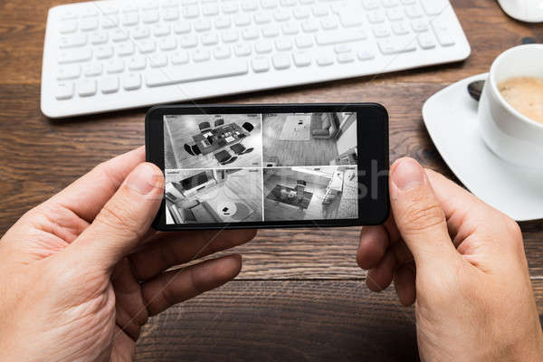Person's Hand Holding Smartphone And Monitoring Video Footage Stock photo © AndreyPopov
