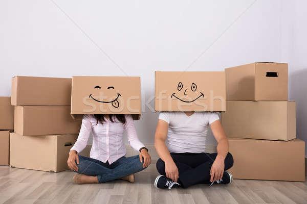 Happy Couple Lying On Floor Wearing Cardboard Boxes Stock photo © AndreyPopov