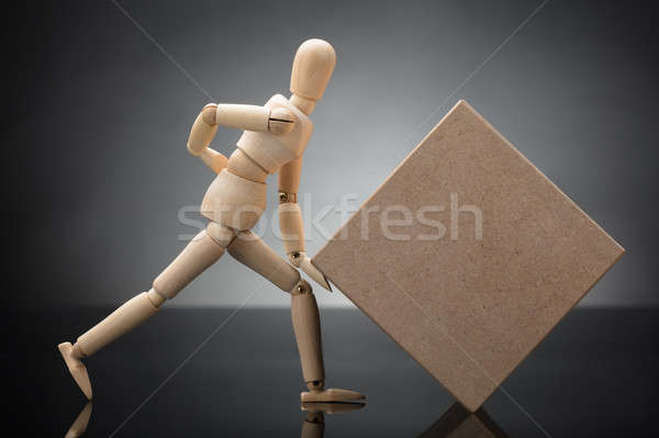 Wooden Dummy Lifting Cardboard Box Suffering From Back Pain Stock photo © AndreyPopov