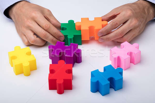 Person's Hand Solving Jigsaw Puzzle Stock photo © AndreyPopov
