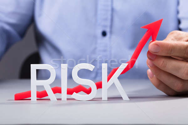 Person Holding Increasing Arrow Behind The Risk Text Stock photo © AndreyPopov