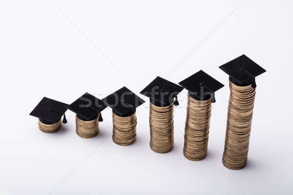 Elevated View Of Increasing Stacked Coins With Graduation Hat Stock photo © AndreyPopov