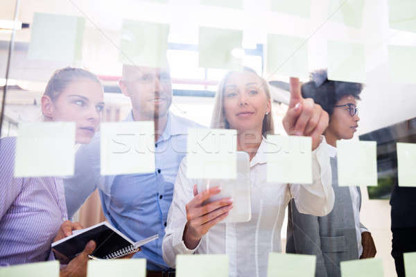 Group Of Businesspeople Sticking Adhesive Notes On Glass Wall Stock photo © AndreyPopov