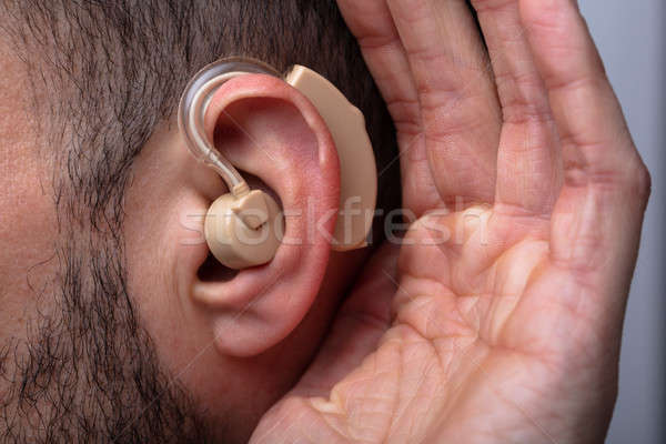 Man Inserting Hearing Aid In His Ear Stock photo © AndreyPopov