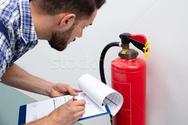 Férfi tűzoltó készülék ír irat közelkép fiatal Stock fotó © AndreyPopov