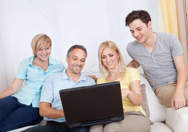 Family together sitting on the couch with laptop Stock photo © AndreyPopov