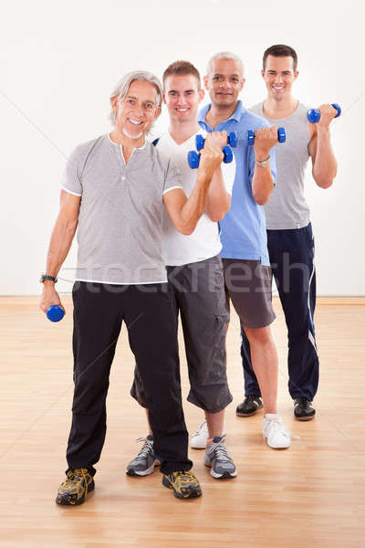 Row of men working with dumbbells Stock photo © AndreyPopov