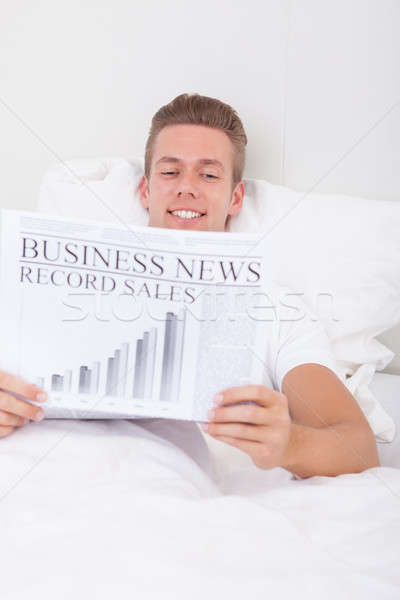 Young Man Lying On Bed Reading Newspaper Stock photo © AndreyPopov